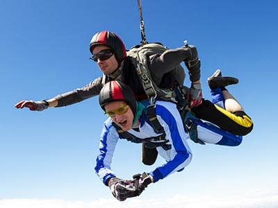 A man skydiving with an instructor on his back