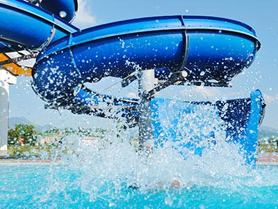 Someone coming down a blue water slide and making a large splash in the pool