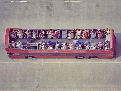 Bird's eye view of people sat on the top deck of a red open bus, driving on a road