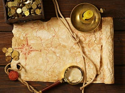 A treasure map with a magnifying glass, candle and coins to the side of it