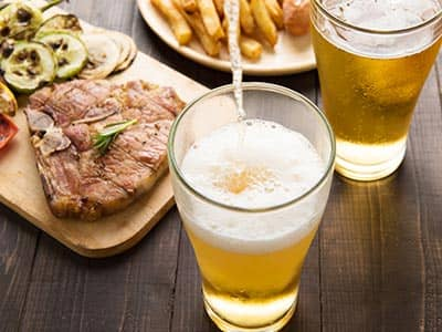 Two pints of beer with a steak meal on a wooden board and some chips behind it