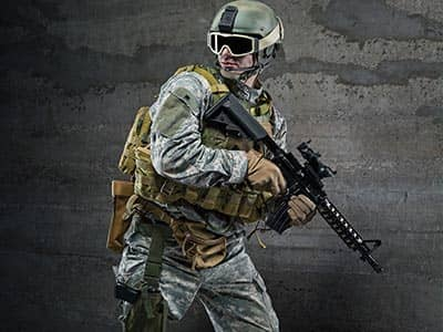 A man in camouflage gear and a helmet, holding an air rifle