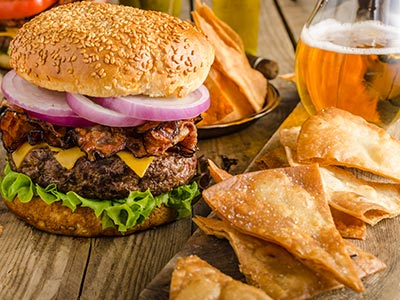 A burger meal with some Doritos and a beer on the side