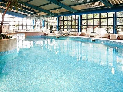 An indoor pool at Mercure Abbots Well, with sun loungers around the side