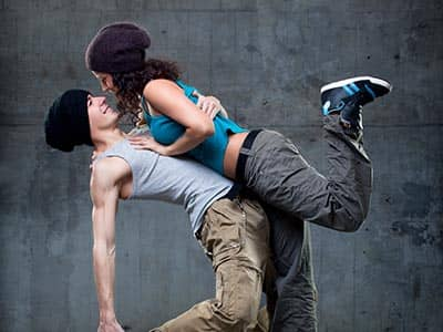 A man lifting up a woman and breakdancing