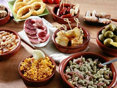 Various tapas dishes in red bowls, set out on a wooden table