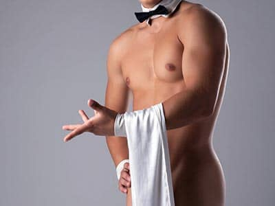 A semi-naked man, in a bowtie, holding a white towel over his body