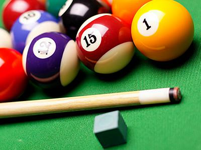 Close up of snooker balls next to a cue