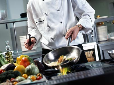 A professional chef cooking in a kitchen, with ingredients on the side