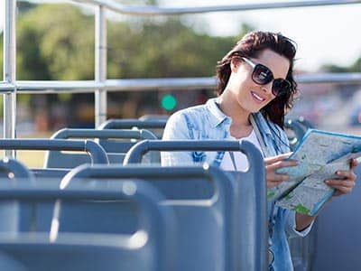 A woman reading a map and sat on the top deck of an open top bus