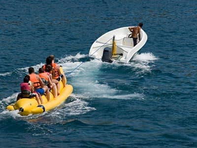 People on a banana boat in the sea, being pulled by another boat