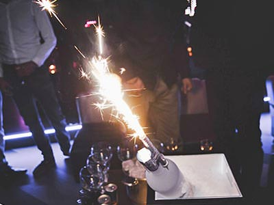 A bottle of alcohol with a sparkler in