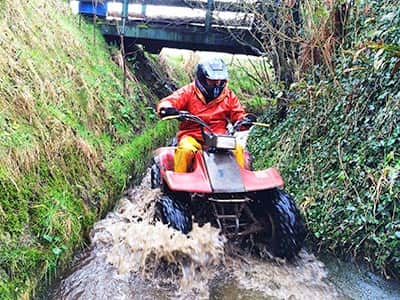 A man driving a quad bike through a river