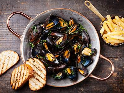 Mussels in a bowl, with bread on the side and a small bowl of chips