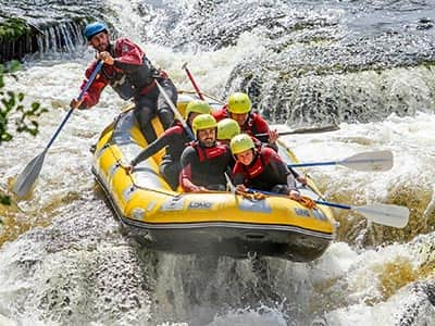 People white water rafting in a river