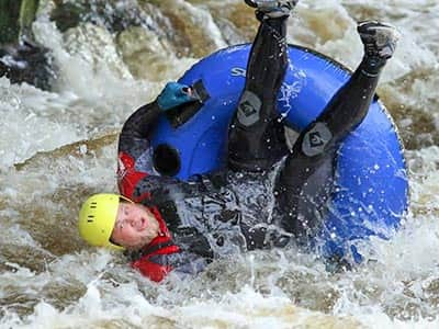 A man falling out of a rubber dinghy and into water