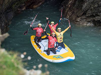 Four people with their hands in the air on a supersized SUP board in the water