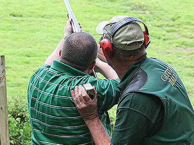 A man aiming with a shotgun to the sky, as an instructor looks on and holds his arm
