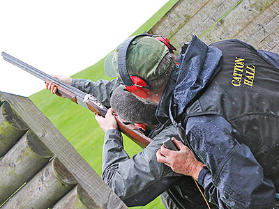 A man aiming with a shotgum with an instructor looking on behind him