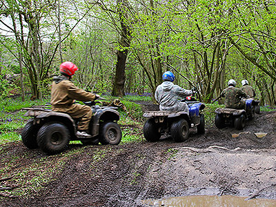 Line of people driving quad bikes through a muddy path in a forest