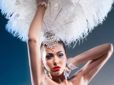 A woman posing whilst wearing a large white feather headdress