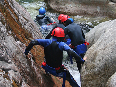 Four people walking along the bottom of a cliffside into water