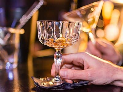 A man's hand holding a crystal glass stem, with rum in