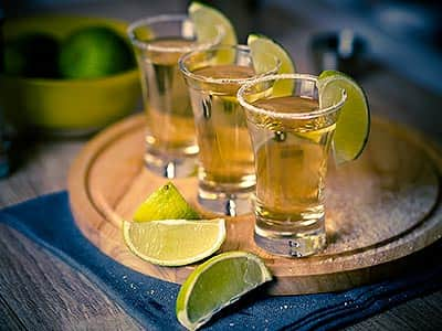 Three shots of tequila on a wooden board, surrounded by slices of lime