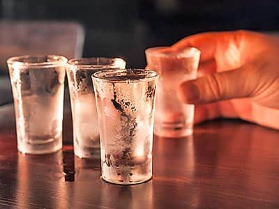 A man's hand holding a shot of vodka, with three other shots in the foreground