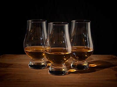 Three glasses with brandy, lined up on a wooden table to a dark backdrop