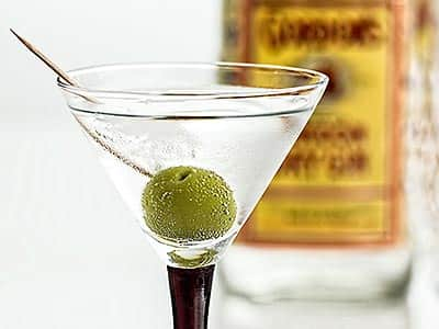 A martini glass of gin with a green olive in, and a blurred bottle of gin in the background