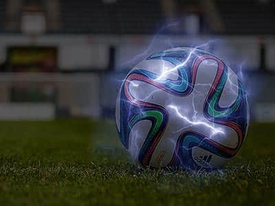 Electric sparks around a football on a pitch