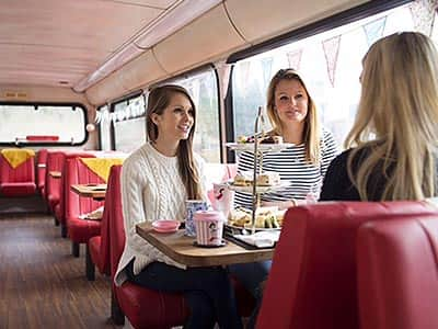 Three girls sitting on a bus, eating afternoon tea