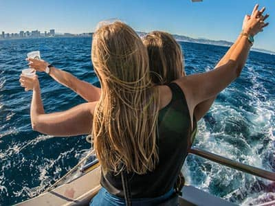 The back of two women on a boat, to a backdrop of the sea