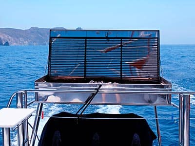 A bbq on the deck of a boat, to a backdrop of the sea