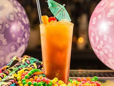 A cocktail placed next to colourful beads, with balloons in the background