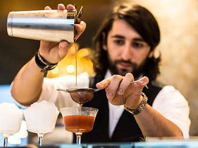 A barman pouring a cocktail into a glass, through a sieve