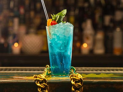 A blue cocktail on a bar top