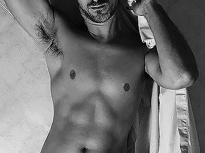 Black and white image of a semi-naked man, holding a white shirt over his shoulder