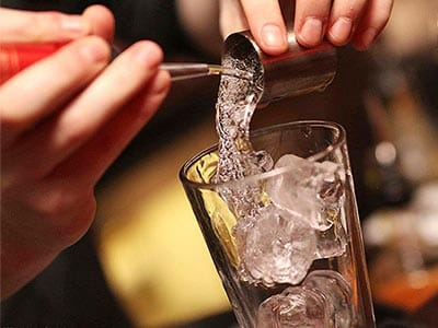 A man's hands pouring liquid over ice in a glass