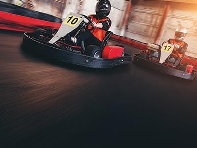 Close up of two people racing on a go karting track