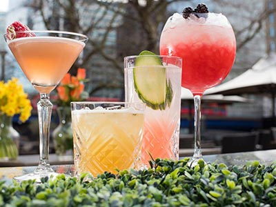 Four different cocktails lined up on a bar outdoors