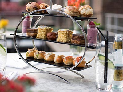An afternoon tea on three tiers, surrounded by drinks