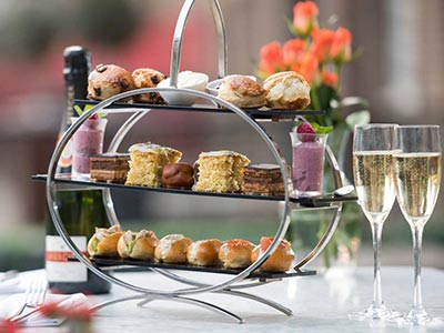 An afternoon tea on two tiers with two glasses of Champagne by the side