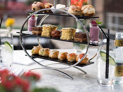 An afternoon tea on two tiers with a glass of water on either side