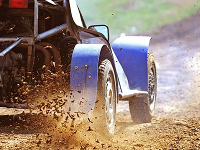 The wheels of a buggy driving through a muddy puddle