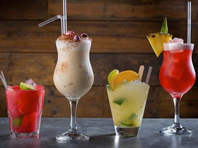 Four cocktails lined up on a bar, all different colours and sizes