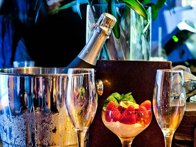 A bottle of Champagne in an ice bucket, next to two flutes on a table