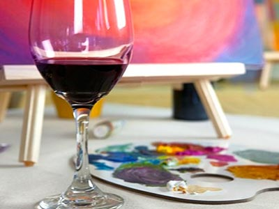 A glass of wine next to an art pallet, with a canvas in the background