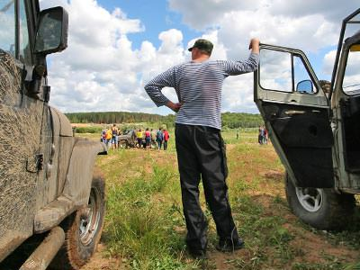 Close up of the back of a man leaning on an open car door of a jeep, next to another jeep in a field